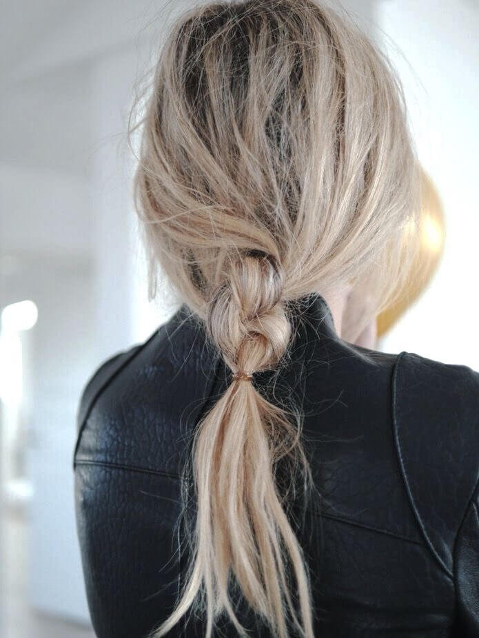 Girl with a short messy braid while wearing a leather jacket.