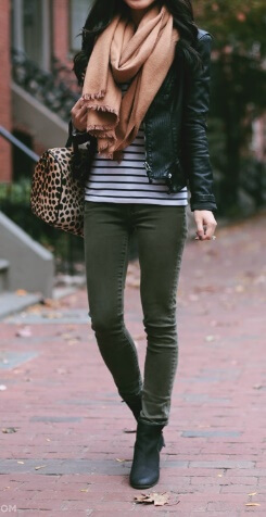 A silky oversized scarf makes a glamorous addition to this outfit of khaki pants, a striped top and leather jacket.
