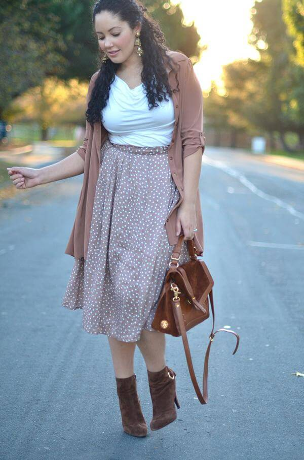 A midi skirt is apt for cooler fall temperatures. Throw on a long cardigan and your trusty brown suede booties for a well put together look that is ideal for work.