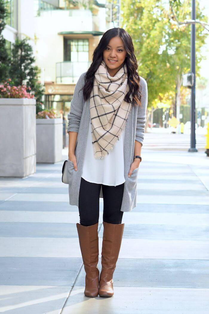 Add some drama to your black and white look with a checkered scarf, a long cardigan, and brown boots.