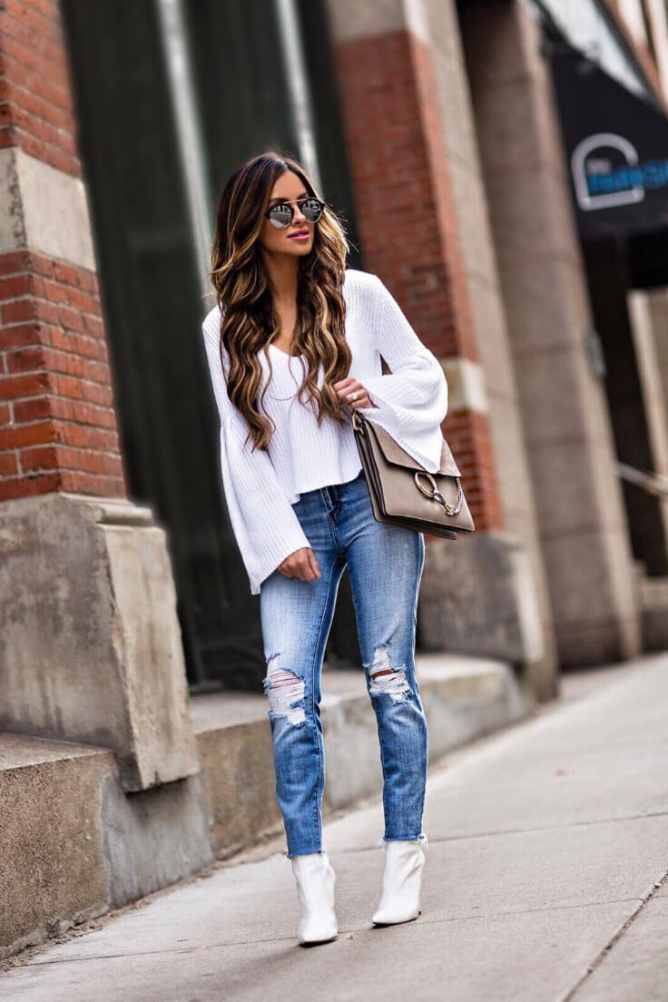 A white top with blue jeans is a classic combination that you can't go wrong with. Add a twist by wearing a sweater top with exaggerated sleeves and let your jeans sit casually on top of your booties.