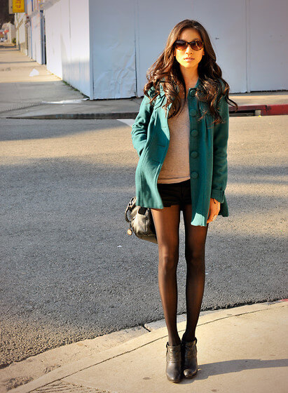 Pair your simple black shorts with black stockings, a grey tee, booties, and a colored jacket.