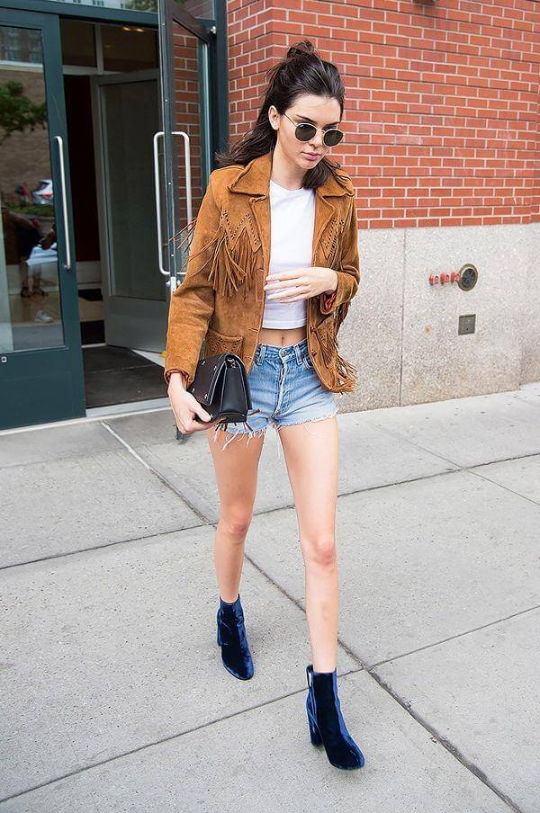 "Take your ""crop top and shorts"" look from summer to fall by throwing on a suede fringed jacket and blue velvet booties."