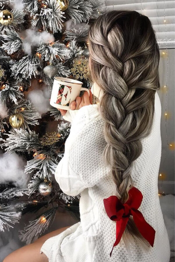 A loose French braid with a big red bow is Holiday perfection