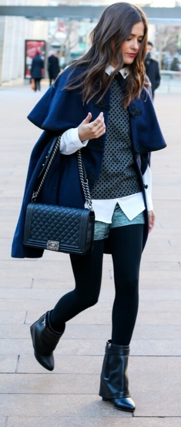 Great layering with a voluminous coat and a mix of quirky layers underneath: a white button-down shirt, printed sweater, black leggings and denim shorts
