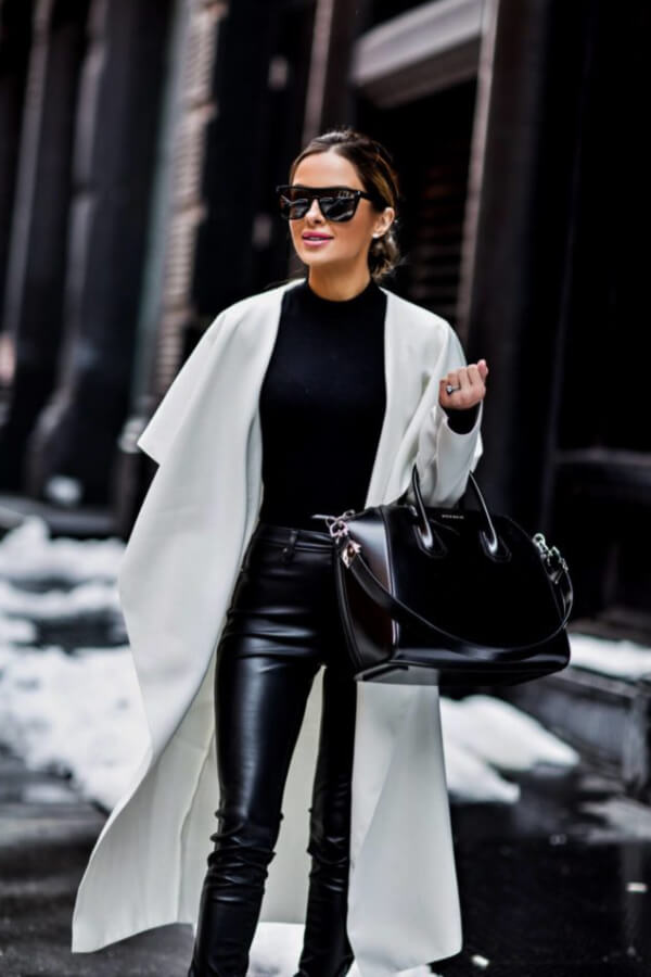 Invited to a snazzy fashion event with nothing to wear? Think cozy and pair black leather with a luxurious draped white coat.