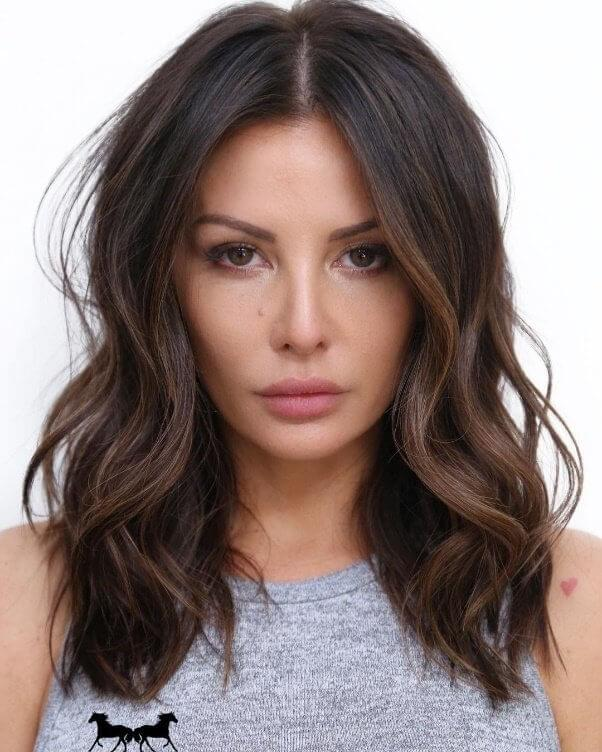 Choose a straight middle parting to add structure to a bob cut of tousled waves