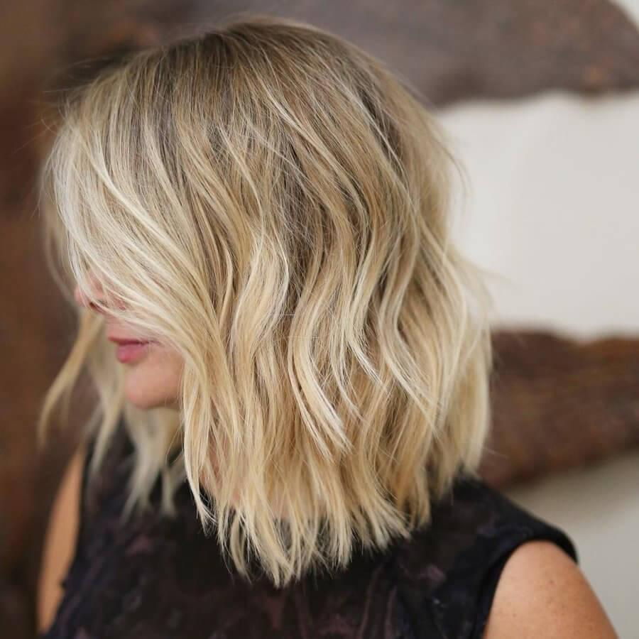 Give volume to fine blonde hair with a sharp-edged bob cut into long blunt layers