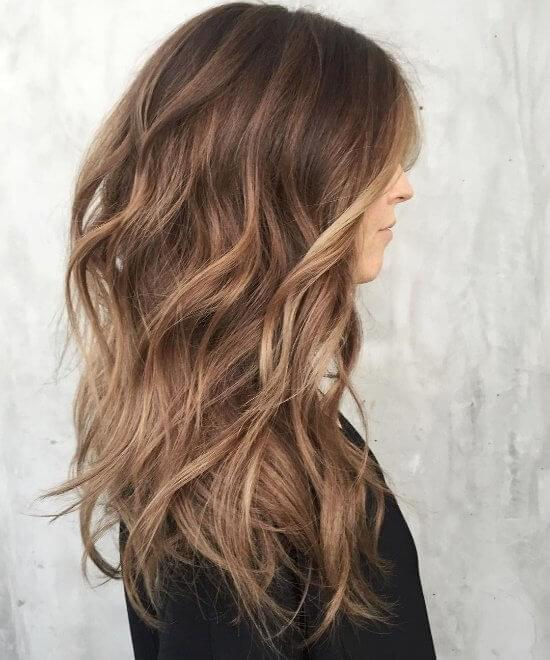Halfway between blonde and brown, this caramel hair color adds bounce and body to this layered cut