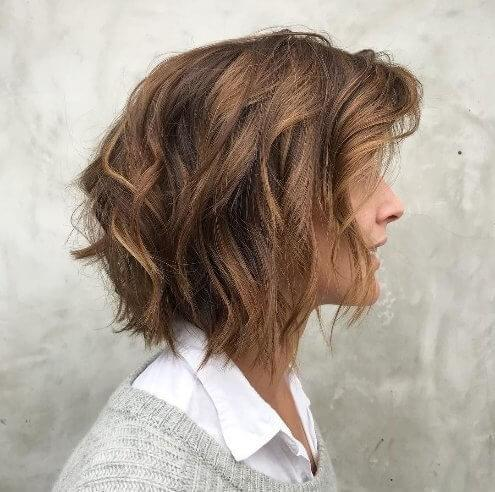 Wake up a tired head of hair with rich caramel highlights on an uneven wispy bob