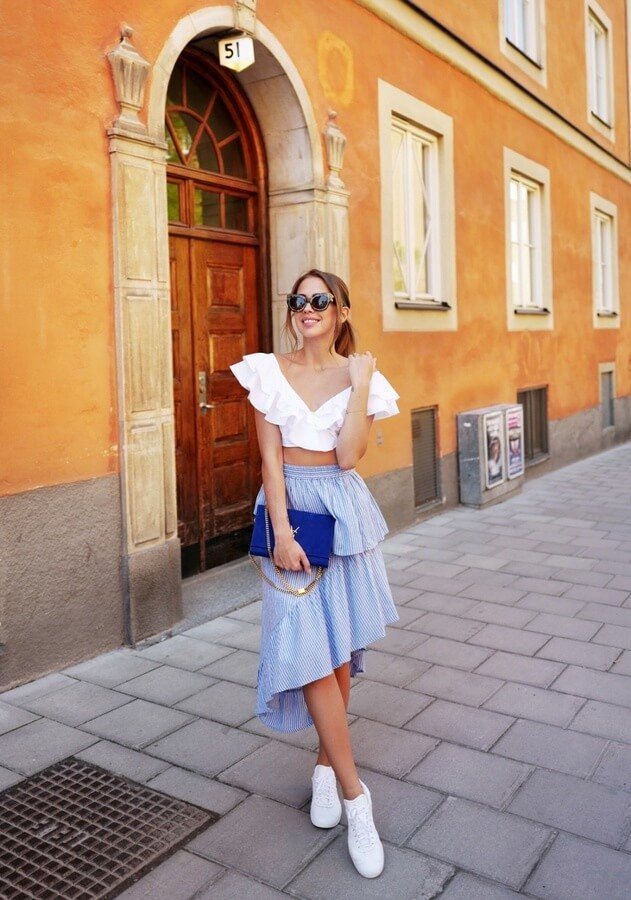It's time to switch things up and leave that mini skirt for an asymmetrical shape with ruffles. Light blue is the perfect color for the summertime. Paired with a white crop top is the ideal outfit to walk around and discover a Greek island.
