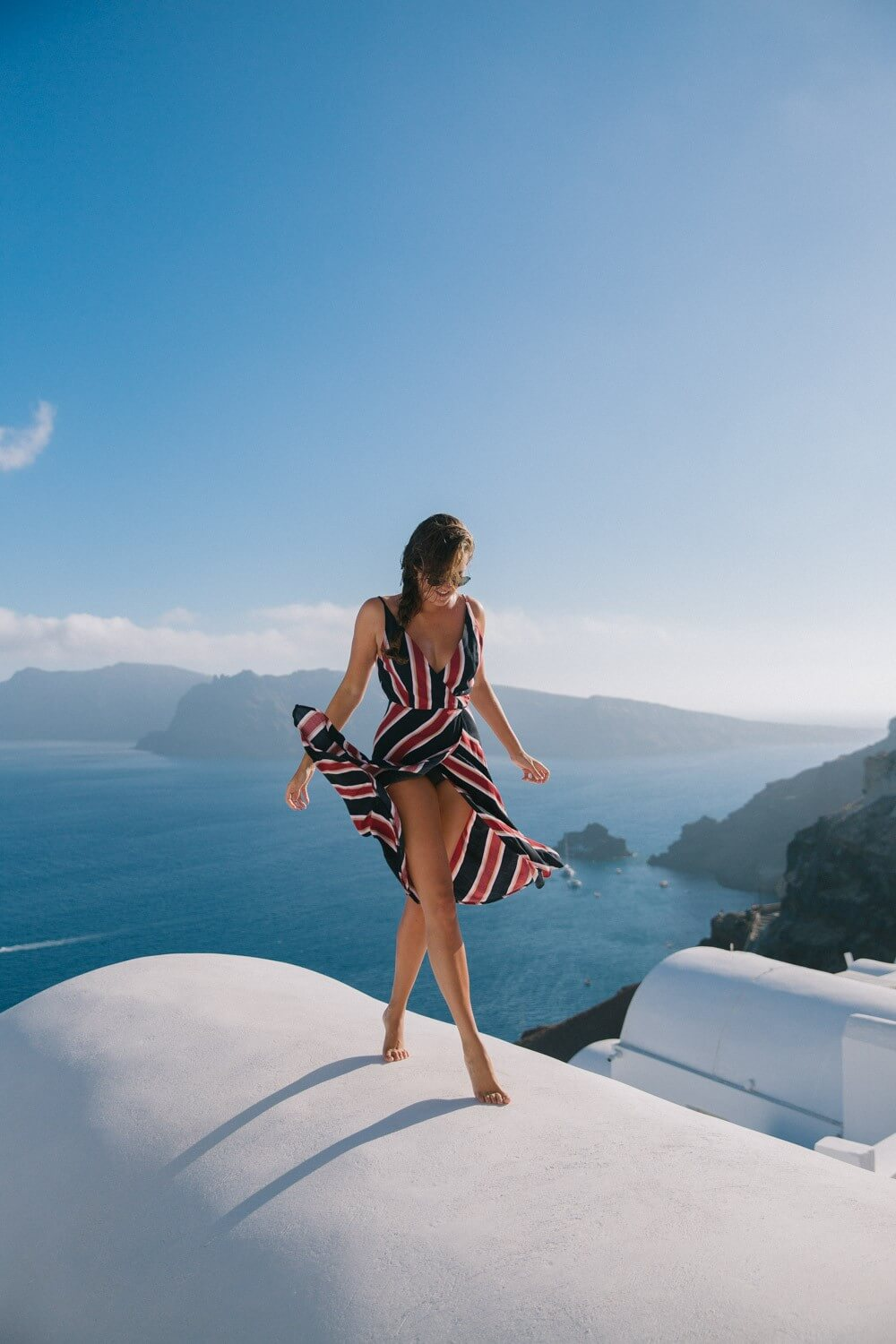 Wrap yourself in the striped red-blue dress on the top of the white house in Santorini. #summerstyle #summerfashion