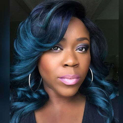 This bold blue hair color is complemented by subtle strands of black and looks stunning on the deeper skin.