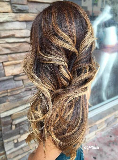 This look mixes strands of blonde and brown, creating a sophisticated and intricate hair color.