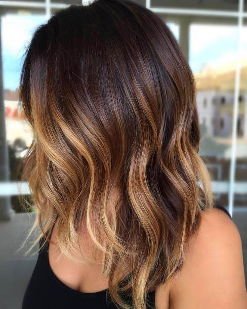 Another ombre beauty, this dark brown look gradually fades into a light blonde color towards the fall of the hair.