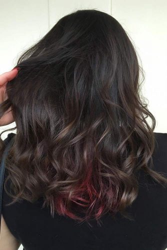 If you're wanting to steer clear from going too bold, experiment with something like this style, as it utilizes a common dark brown ombre base with just a bit of bold red strands.