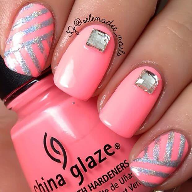Pretty in pink and silver, this design can be achieved with a little bit of striping tape and nail gems, resulting in a cute summer look.
