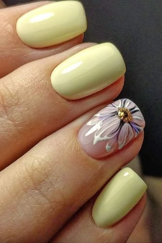 Accenting an adorable soft yellow shade, this detailed flower is painted on a clean nail and perfectly brings together the entire summer look.