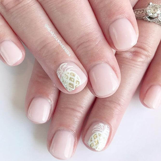Nude, simple, and gorgeous, this nail art adds just the right amount of detail on each accent nail with a white and gold sparkly pineapple.