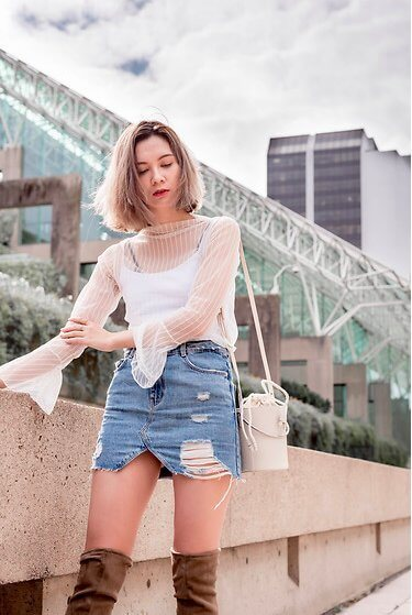 Distressed denim skirt can look very trendy and fancy when you style it with bell bottom sleeves and thigh-high boots. Who said that you couldn't style boots in summer? #sheertop #summeroutfit