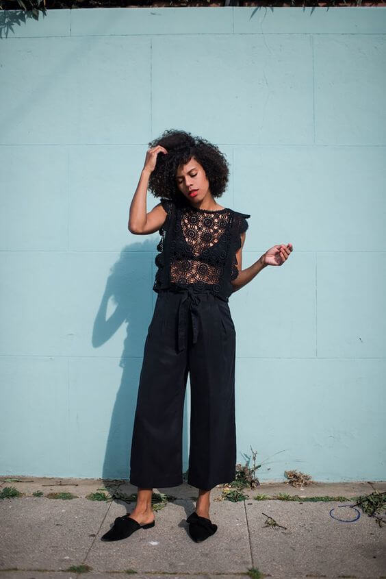Black crochet sleeveless top with ruffles seems very appropriate to style with matchy high waist trousers. Match this look with a pair of trendy pointy-toe mules. #sheertop #summeroutfit