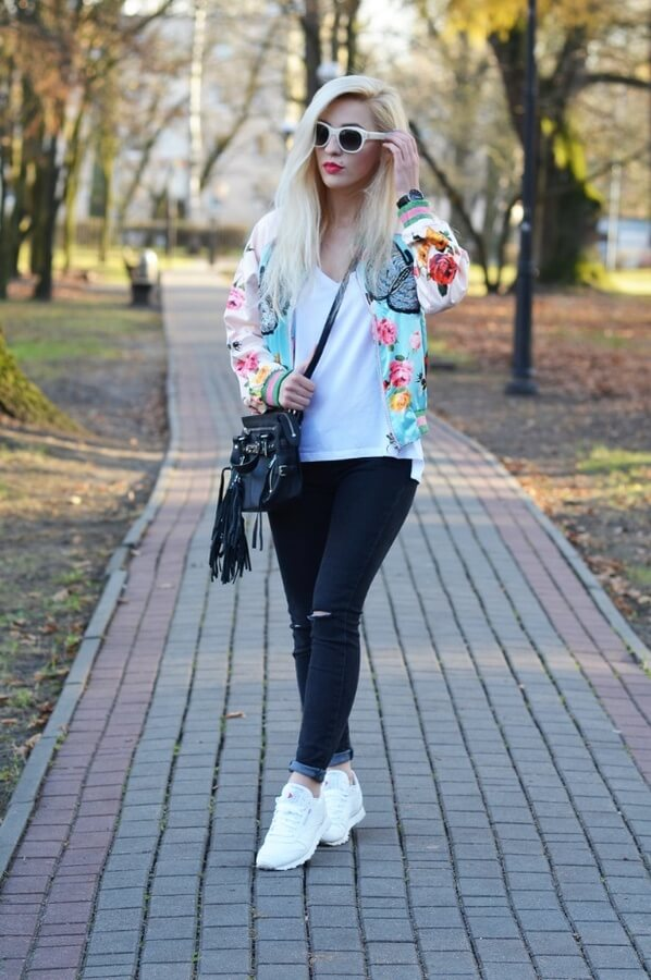 Girl in the park wearing urban ripped jeans with a plain white tee and sneakers – all boosted with an eccentric bomber jacket in floral #floraljacket #jacket #springfashion