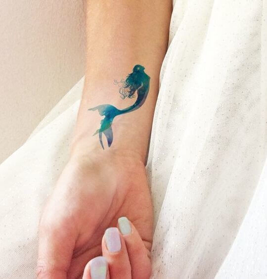 Mermaid seems very feminine, and they are a perfect idea for your summer tattoo! Let it be made of watercolors. #summertattoo #minitattoo #minimalisttattoo #colorfultattoo