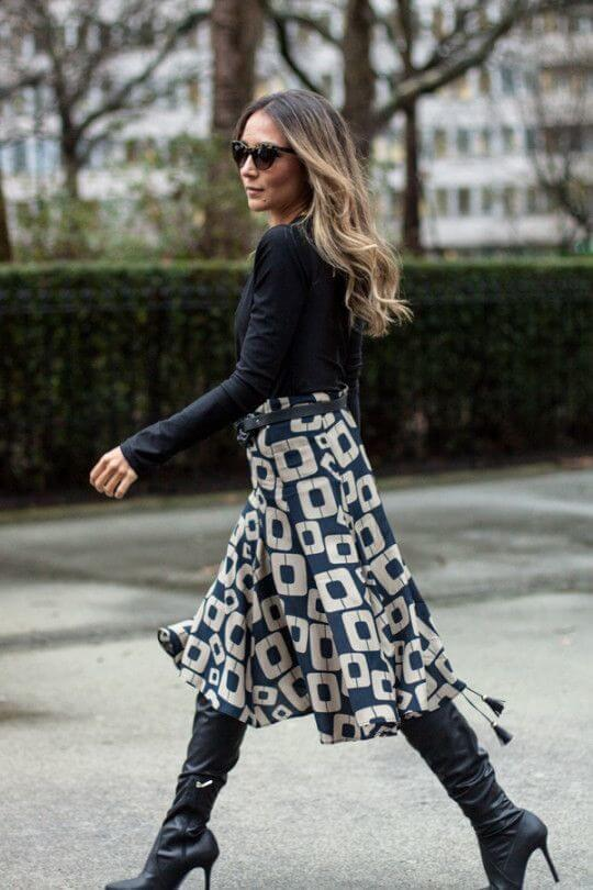 Navy blue boots matched with a printed navy-white midi skirt are perfect workwear inspiration