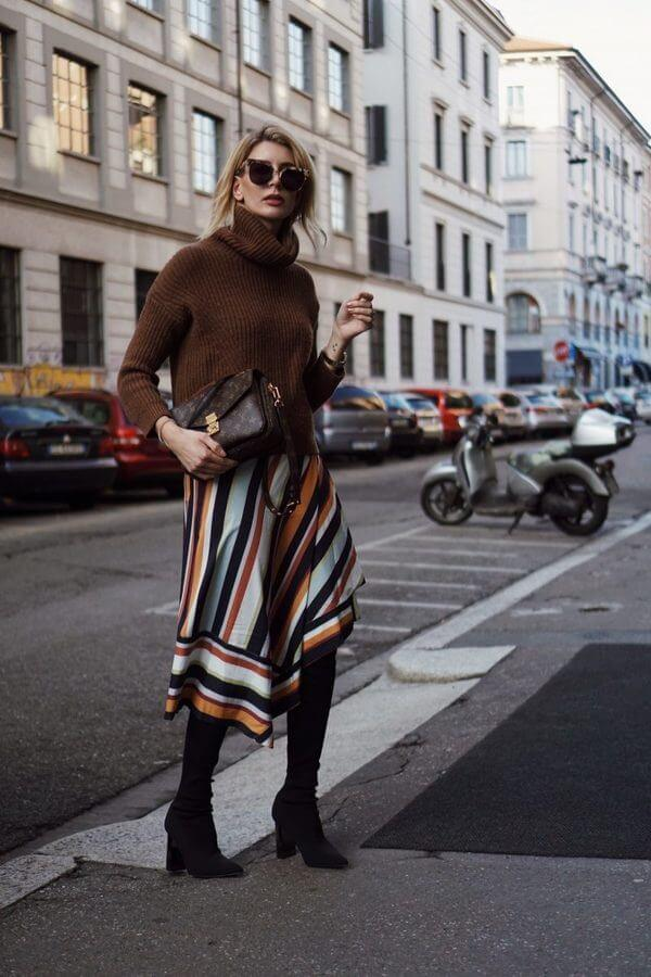 Brown is one of the most popular colors this season. Don't hesitate to style a warm sweater and asymmetric striped skirt with your favorite pair of boots.
