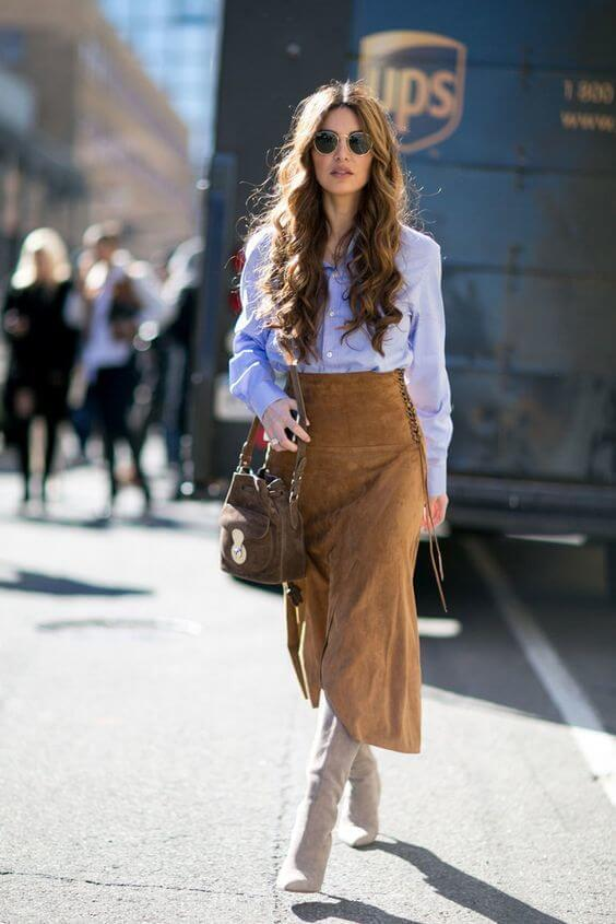Add some bohemian vibes into your workwear with this brown suede skirt and fringes. Round everything off with a blue button-down and beige boots.