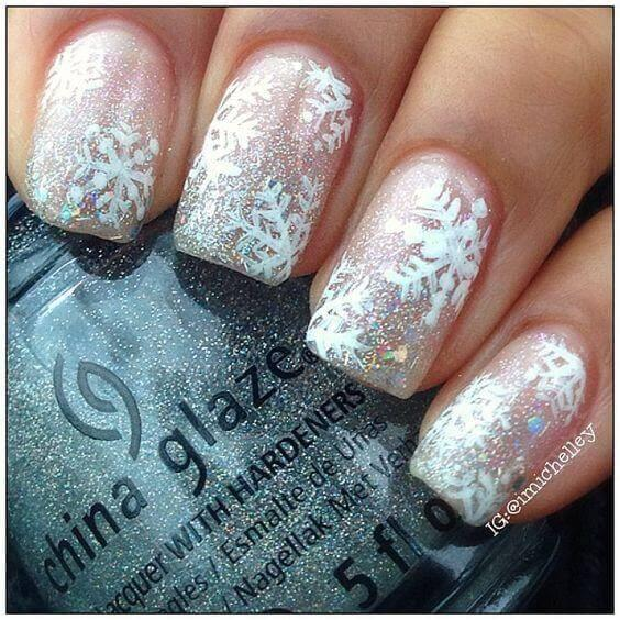 Sparkly nail polish and snowflakes on them will instantly bring you into the holiday spirit. #winternails #naildesign