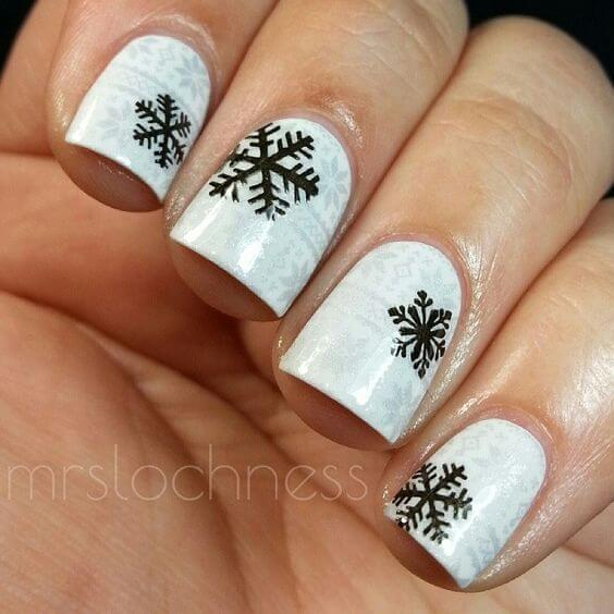 The classic white design is enriched with black snowflakes. Even if it sounds minimal, it is perfect for the winter season. #winternails #naildesign