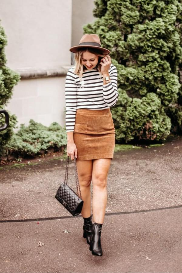 Corduroy is an ideal winter material. A mini skirt can be a chic item if you pair it with a striped shirt, and add beige fedora. For the end, round everything off with stylish ankle booties. #skirtsinwinter #skirtoutif #winteroutfits