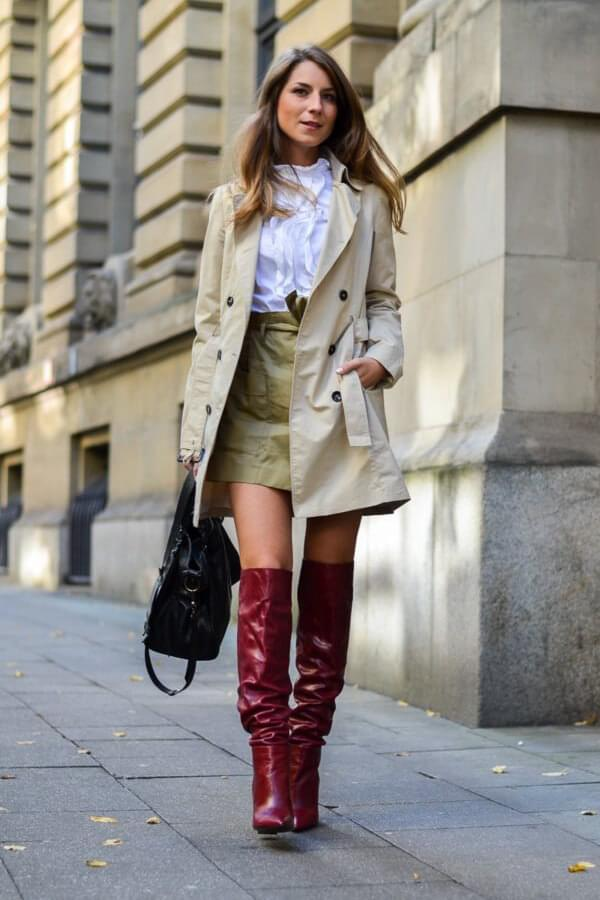 Slouchy boots are one of the main trends for this winter. If you already have purchased one pair of them, don't stop. Pick a perfect khaki wrap mini skirt, match it with a classic white button-down, and a lovely chic trench coat. #skirtsinwinter #skirtoutif #winteroutfits