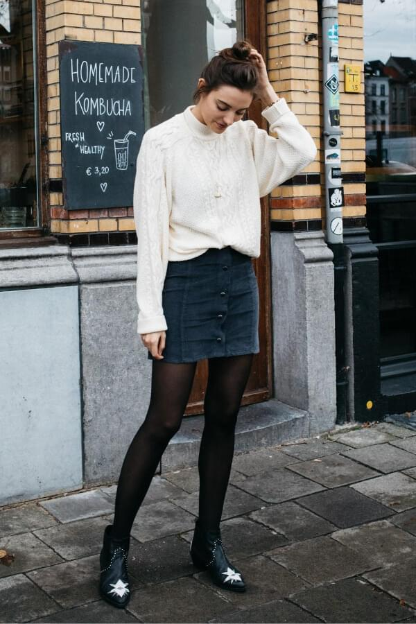 White cable knit sweater is something that you definitely need to own. It is pretty versatile. The blue mini skirt is the perfect item for winter layering. #skirtsinwinter #skirtoutif #winteroutfits