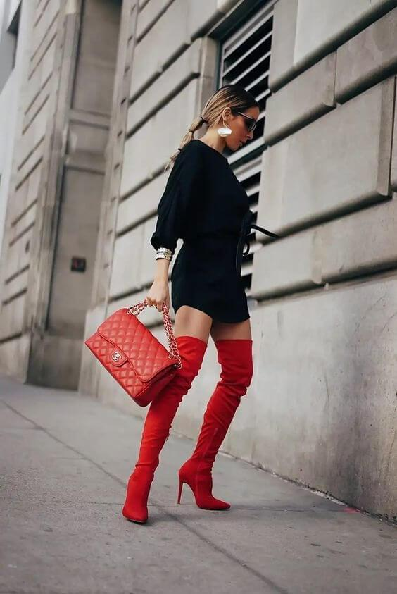 Make a dramatic appearance at the party by wearing red over-the-knee boots with the classic black dress. The red bag is the must-have to match with boots. #bootsoutfit #nighout #nightoutlook