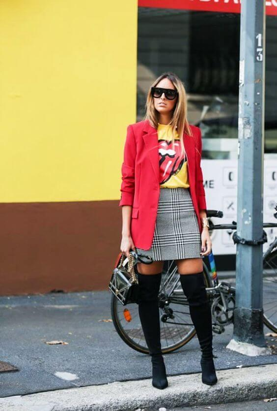 Wearing tees with our favorite band logos on them is a bit cliché, but on the other hand, it is a perfect detail. Style your tee with a checked skirt, blazer in a bright color, and thigh-high boots. #cluboutfit #highboots