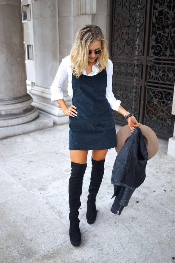 Pinafore dresses make everything easier. You can layer them with a classy button-down below and feel cozy with tall boots that match the color of the dress. #highboots