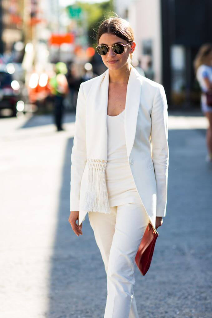 Model in white pants, white top and white blazer, a clutch and statement glasses to accessorize