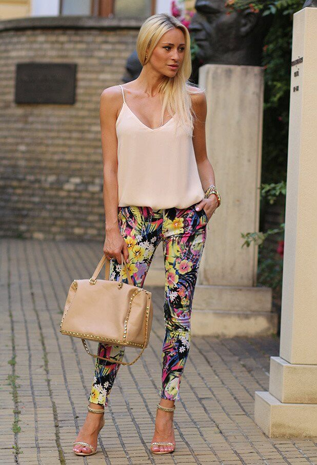 Model wears a beige top and floral pants, sparkly heels and a bag to match