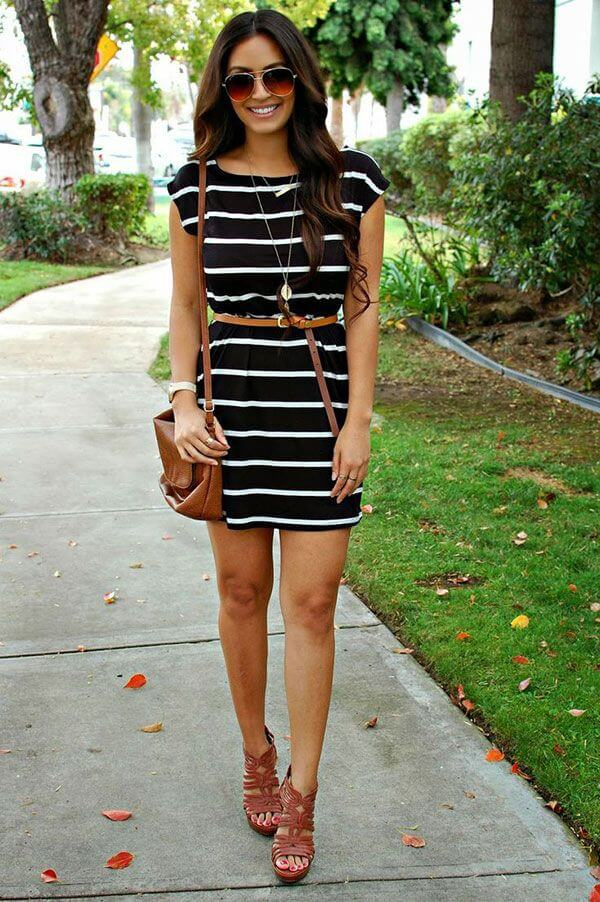 Model looks fearless as shewears a little black and white striped dress, accentuating her hips with a belt, heels for sexiness and a leather bag and statement glasses with a necklace to complete