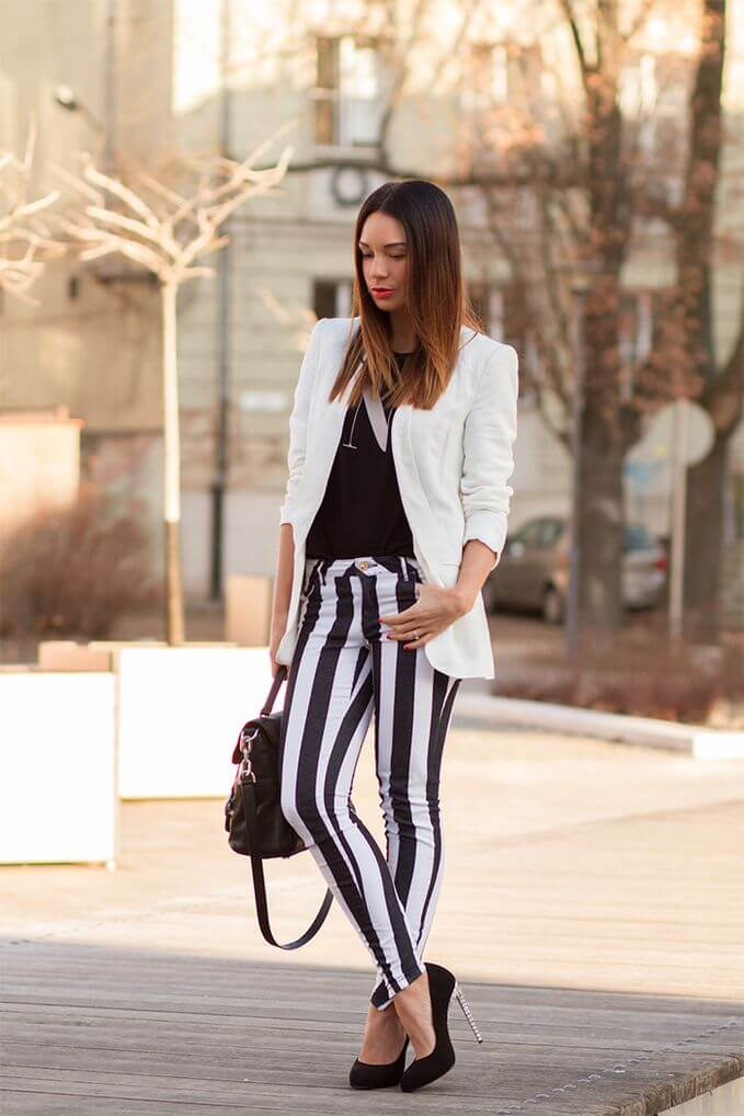 Model pairs her striped pants with a black shirt and white blazers, a black hand bag as her accessory