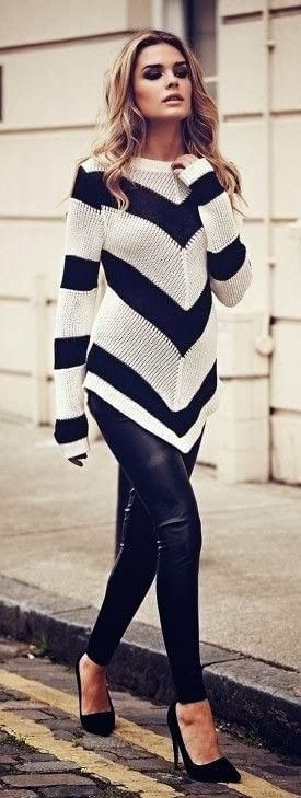 Model walks with a striped sweater and leather pants with black heels to complete