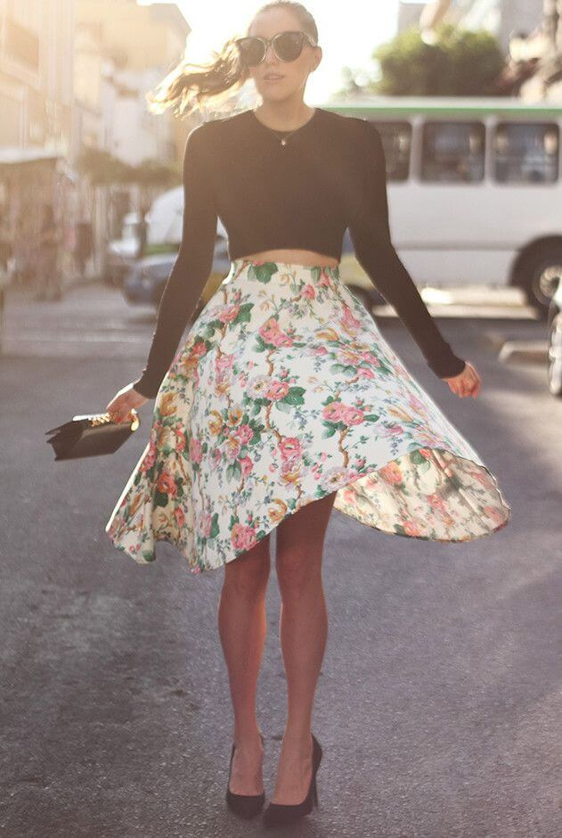 Model looks fun in a plain black crop and floral skirt with heels