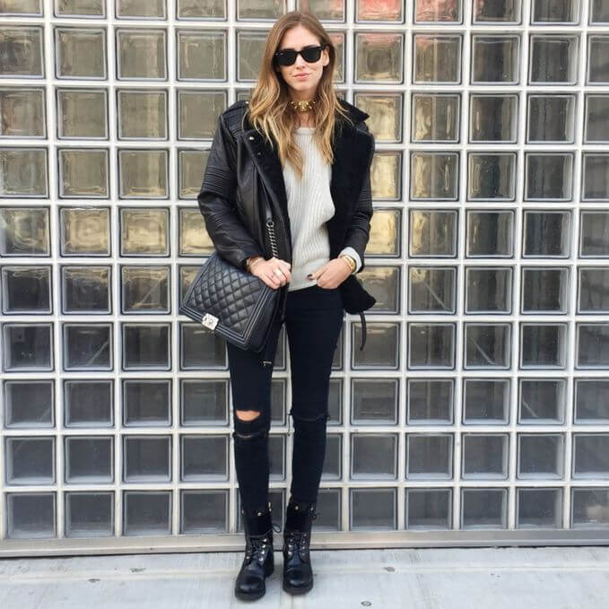 Model is wearing black ripped jeans, black jacket with boots to complete