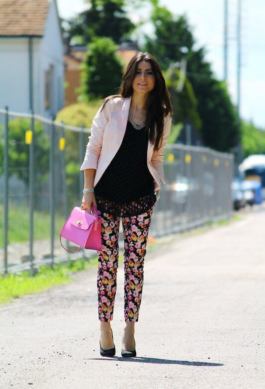 Model wears a black tank with flower print pants with heels, pink blazer and a pink bag to match