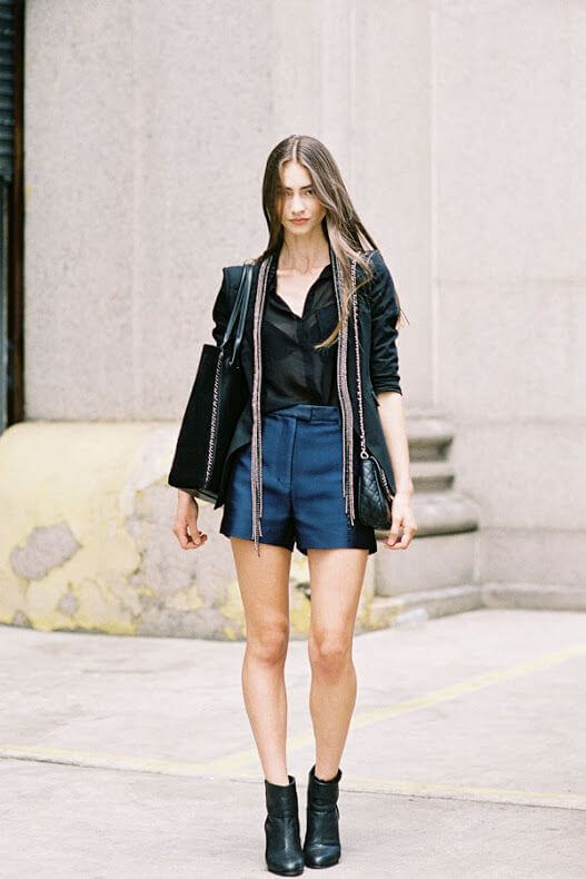 Model in blue high-waisted shorts, black see-through top with blazers, boots and a big shoulder bag to match