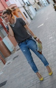 Model poses with a plain shirt adorned with statement necklace, boyfriend jeans and neon heels