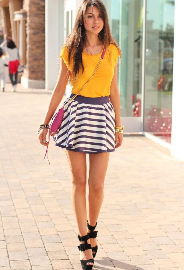 Model struts down the street in a yellow top and striped skirt, a sling bag and sexy black heels