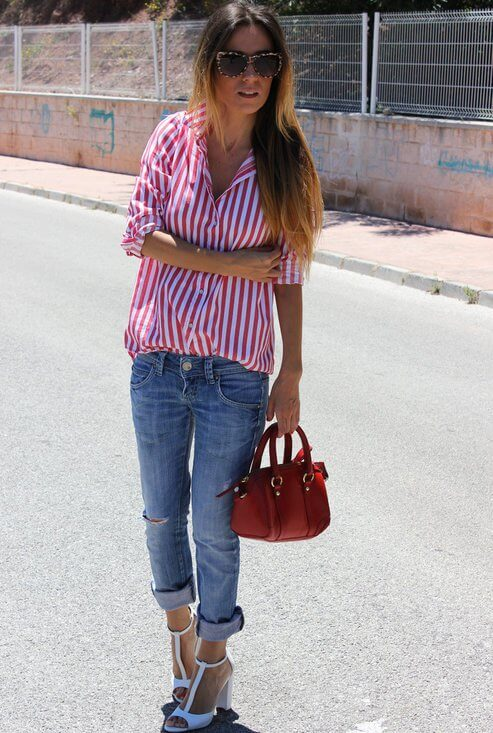 Model is wearing a loose striped shirt with denim pants, white heels and a red handbag